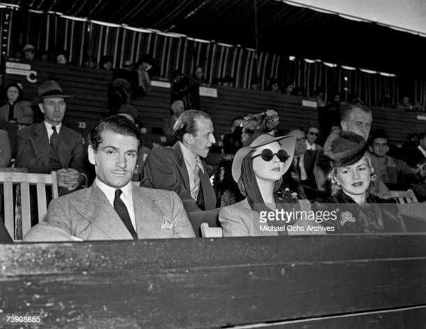 Film and stage actor Laurence Olivier and his wife Vivien Leigh join Claire Trevor at a tennis match at the Pacific Southwest Tournament aka the Los...