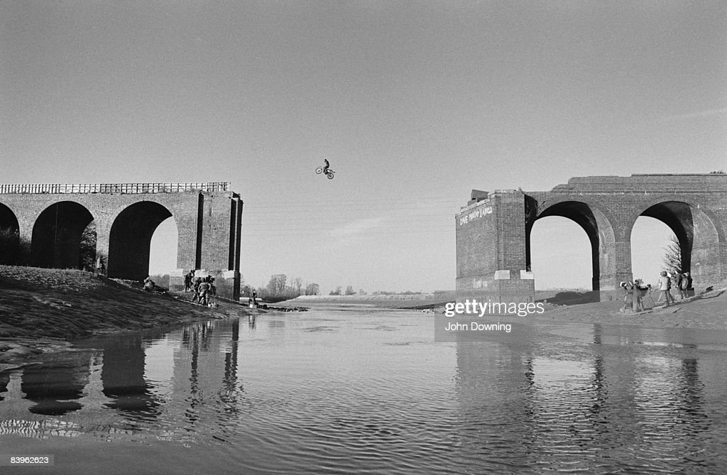A film crew captures a motorcycle leap across a collapsed bridge, circa 1980.