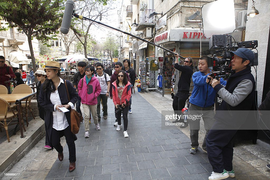A film crew from Chuan Films shoots footage of Zhang Jingchu, a Chinese actress, left, on the set of 'The Old Cinderella' at the Ben Yehuda pedestrian mall in Jerusalem, Israel, on Friday, April 19, 2013. The Bank of Israel governor said Europe remains the weak link in the world economy and European Union officials need to tackle the continent's banking difficulties. Photographer: Ariel Jerozolimski/Bloomberg via Getty Images *** Zhang Jingchu