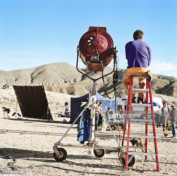 Film crew in desert, spotlight in foreground