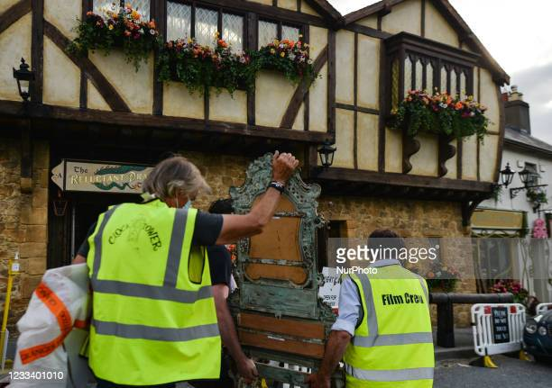 Film crew members carry an old armchair in the center of the village of Enniskerry in County Wicklow. There are only two more days until filming...