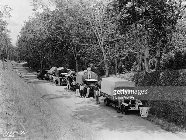 Film crew members standing by their convoy of lorries during the filming of the Paramount Picture 'Booloo'.