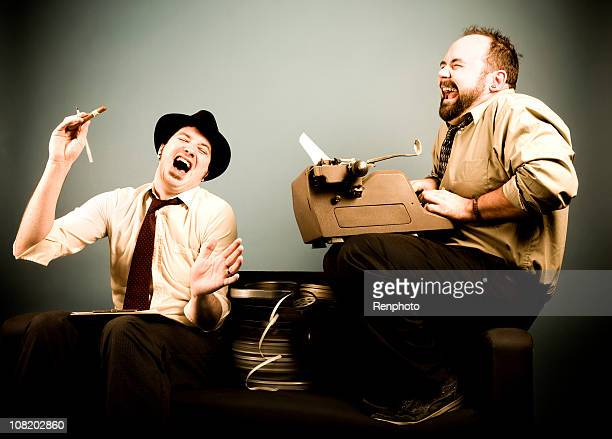 film critics: laughing and typing - authors stock pictures, royalty-free photos & images