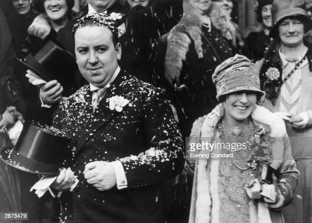Film director Alfred Hitchcock and Alma Reville are showered with confetti after their wedding