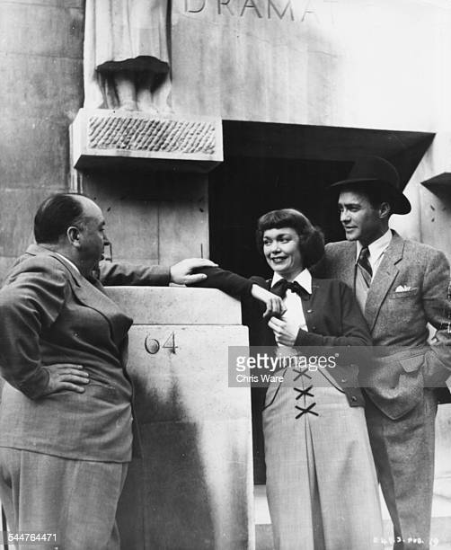 Film director Alfred Hitchcock talking to actors Jane Wyman and Richard Todd stars of his movie 'Stage Fright' outside the entrance of RADA in London...