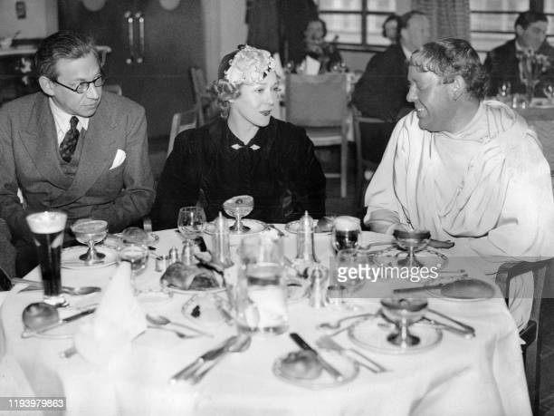 Film director and producer Alexander Korda lunches with Canadian actress Mary Pickford and British actor Charles Laughton wearing his costume from...