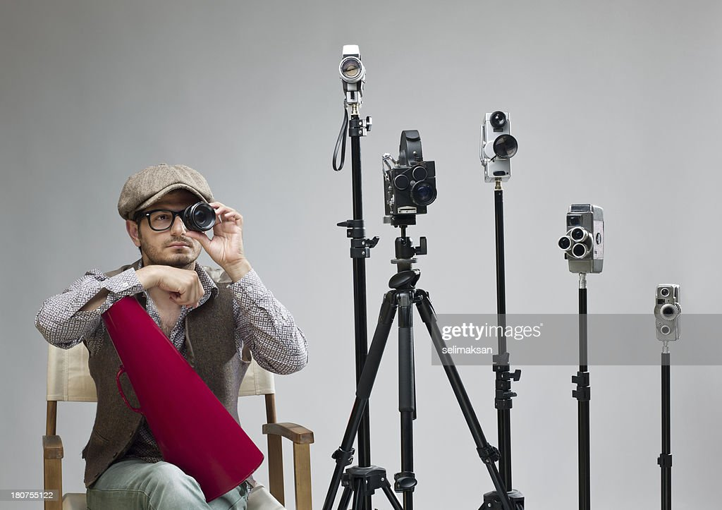 Film director behind camera holding lens for testing : Stock Photo