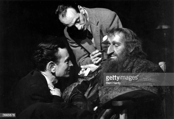 Film director David Lean watches as makeup artist Paul Rabiger works on Alec Guinness transforming him into the role of Fagin in Lean's film...