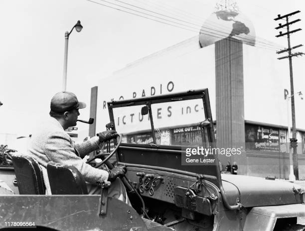 Film director Edward Dmytryk drives a jeep past the RKO Radio Pictures Inc studios on the corner of Gower Street and Melrose Avenue in Los Angeles,...