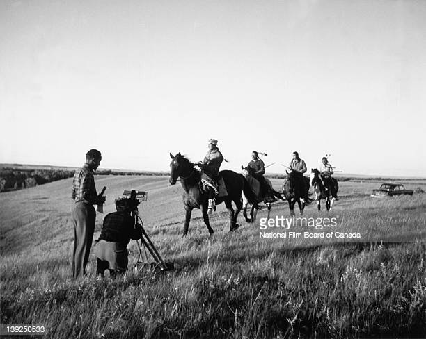 NFB film director Grant McLean and Ron Alexander assistant cameraman shoot on location an historical scene with First Nations men dressed in...