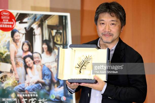 Film director Hirokazu KoreEda poses with the Palme d'Or during a press conference on arrival at Haneda Airport on May 23 2018 in Tokyo Japan