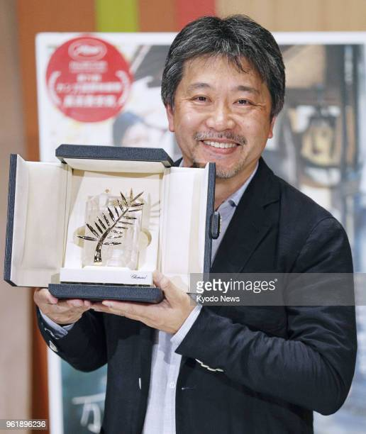 Film director Hirokazu Koreeda shows off the Palme d'Or trophy during a press conference upon his arrival at Haneda airport in Tokyo on May 23 2018...
