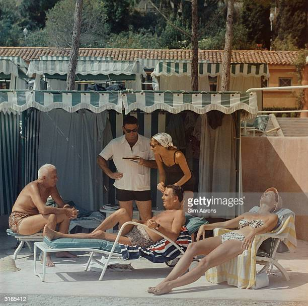 Film director Howard Hawks and his wife Dee spend a summer day by the pool in Monaco with producer Charles K Feldman and Feldman's protegee Germaine...