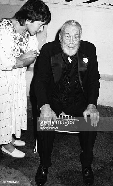 Film director John Huston and his aide Maricela Hernandez attending the post Academy Awards party at Spago's restaurant in Los Angeles March 24th 1986