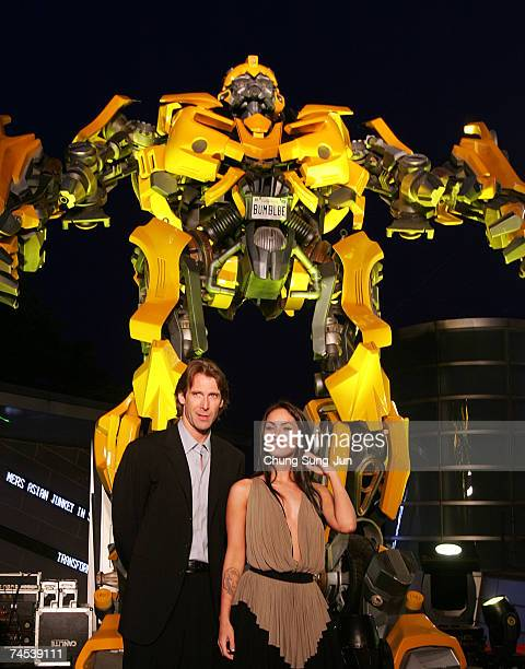 S film director Michael Bay and actress Megan Fox attend in front of Bumble Bee before a press conference to promote their new film Transformers on...