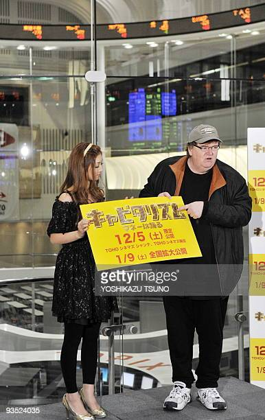 US film director Michael Moore and Japanese actress Yuko Ogura display a board which says his movie 'Capitalism A Love Story' will be screened from...