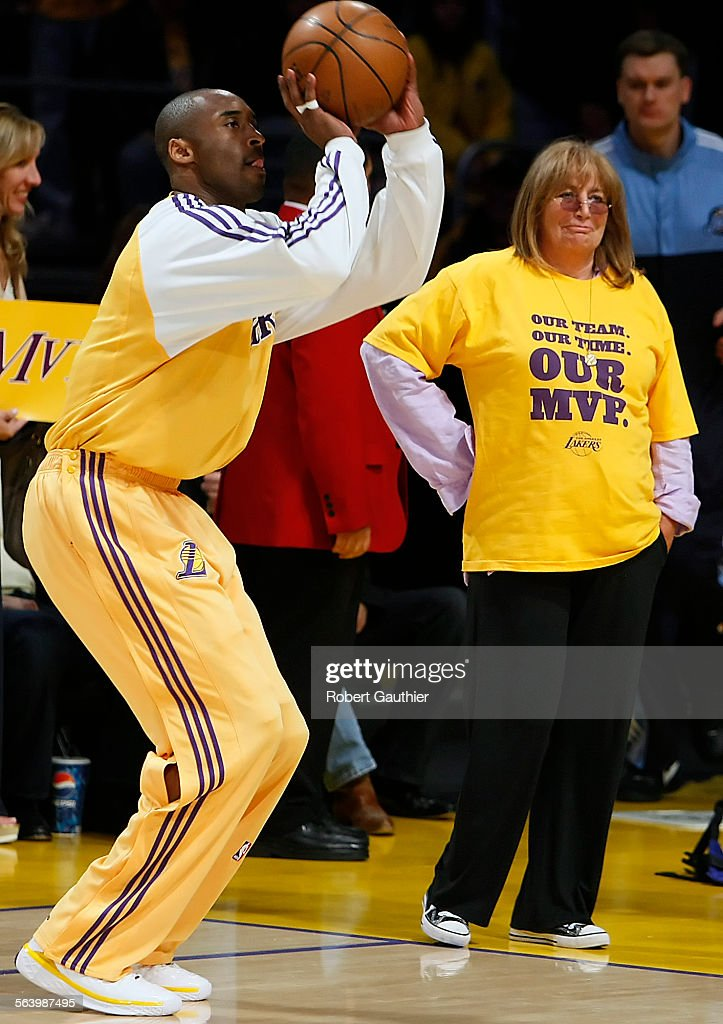 Film director Penny Marshall looks on from the sideline as NBA MVP Kobe Bryant warms up before game : News Photo