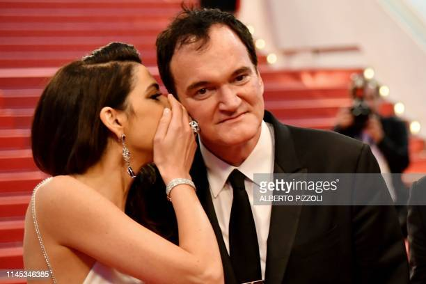 US film director Quentin Tarantino listens to his wife Israeli singer Daniella Pick as they pose before leaving the Festival Palace after the...