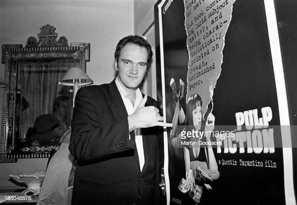 Film director Quentin Tarantino, portrait, standing by a poster for his film 'Pulp Fiction', London, United Kingdom, 1994.