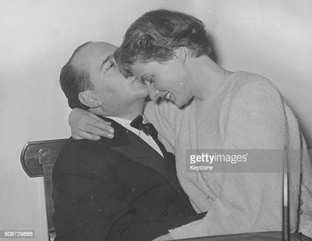 Film director Roberto Rossellini kissing his wife actress Ingrid Bergman on the cheek as the pair embrace following her successful debut in the play...
