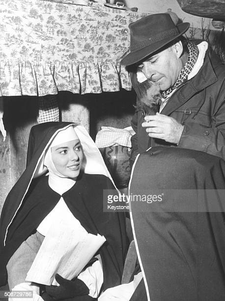 Film director Roberto Rossellini talking to actress Giovanna Ralli who is wearing a nun's habit on the set of the film 'Escape by Night' circa 1960