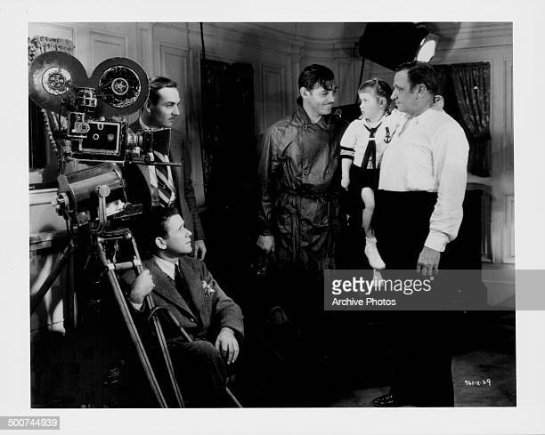 Film director Tay Garnett actor Clark Gable and actor Wallace Beery with his daughter Carol Ann on the set of the movie 'China Seas' 1935