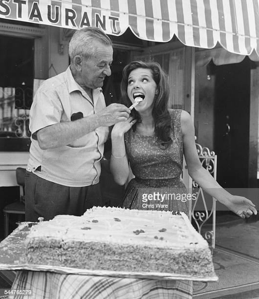 Film director William Wyler feeding cake to actress Samantha Eggar on her birthday on the set of the film 'The Collector' in London July 1st 1964