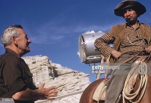 Film director William Wyler talking to a cast member on the set of his western 'The Big Country'
