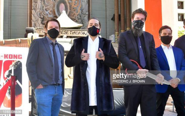 Film directors Gareth Edwards, Jordan Vogt-Roberts, Adam Wingard and Michael Dougherty pose after cutting the ribbon marking the reopening of the TCL...