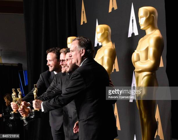 Film editor John Gilbert winner of the award for Editing for 'Hacksaw Ridge' poses with presenters Michael J Fox and Seth Rogen in the press room...
