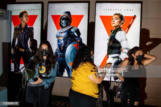 Film fans pass through security in the lobby of the El Capitan Theatre, in Hollywood, CA, with posters on display for Marvel Studios Black Widow,...