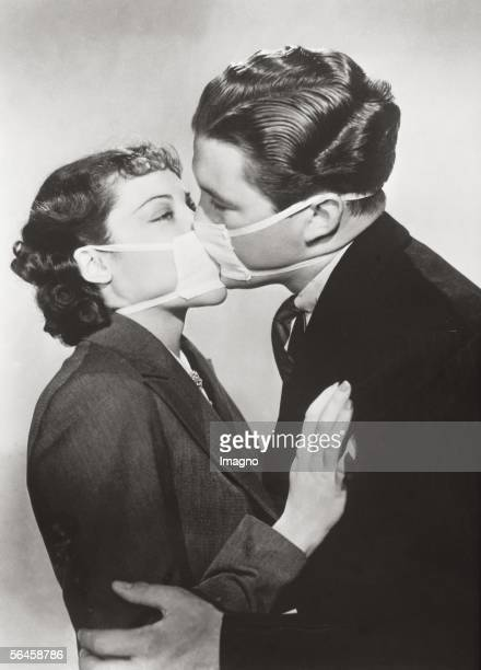 Film kiss with protective mask to prevent infection during a flu epidemic in Hollywood. Photography. 1937. [Filmprobe einer Kussszene mit...