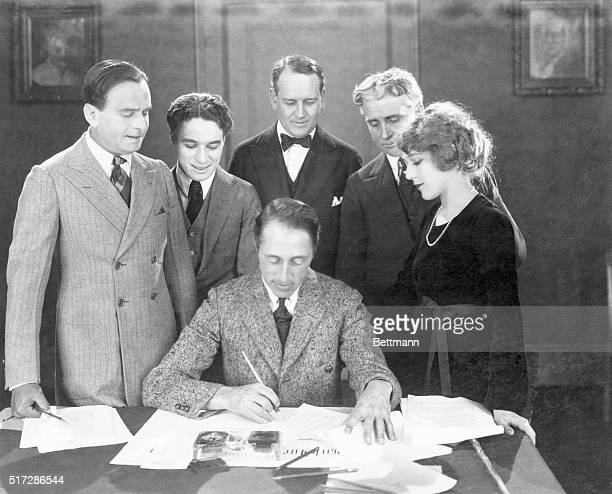 Film maker DW Griffith reviews the contract of actress Mary Pickford her first with United Artists The actress is accompanied by fellow film stars...