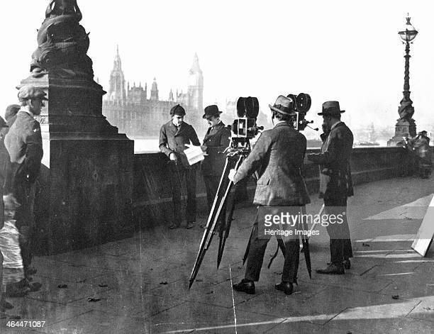 Film makers on the Albert Embankment London Two men stand by the wall looking at a some papers They are being filmed by two cameramen with their...