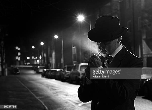 Film NoirYoung man in suite, lighting cigarette