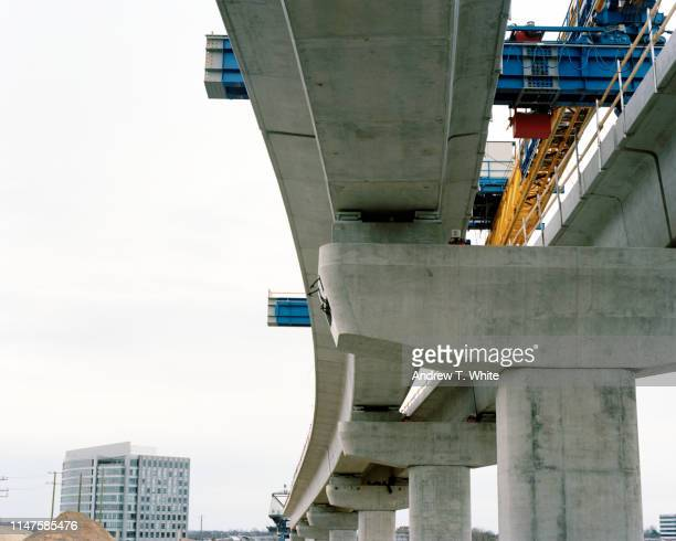 film photograph of dc metro silver line being built in tyson corner from directly below the elevated section of track - bridge built structure stock pictures, royalty-free photos & images