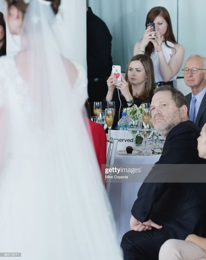 Film Producer Harvey Weinstein looks on as a model walks the runway during the Marchesa Spring 2015 Bridal collection show at Canoe Studios on April 11, 2014 in New York City.