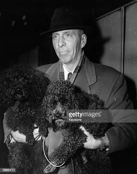 Film producer Howard Hawks with his poodles Trix left and Susie right at Waterloo Station London where he is taking the Queen Mary Boat Train en...