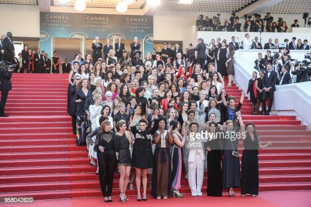 Film representatives pose on the red carpet in protest of the lack of female filmmakers honored throughout the history of the festival at the...