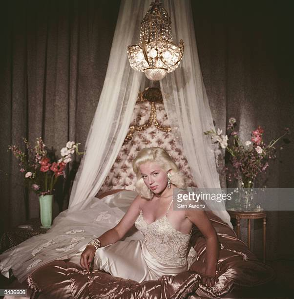 Film star Diana Dors in blonde bombshell pose on a satin covered bed