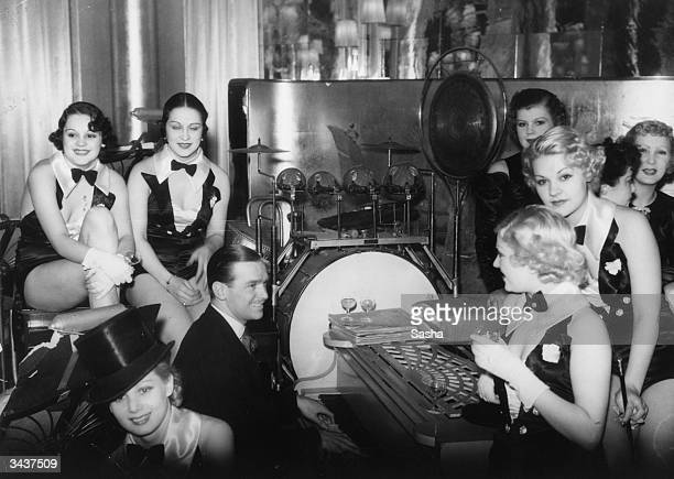 Film star Douglas Fairbanks Jnr playing the piano at Grosvenor House Hotel surrounded by a bevy of chorus girls