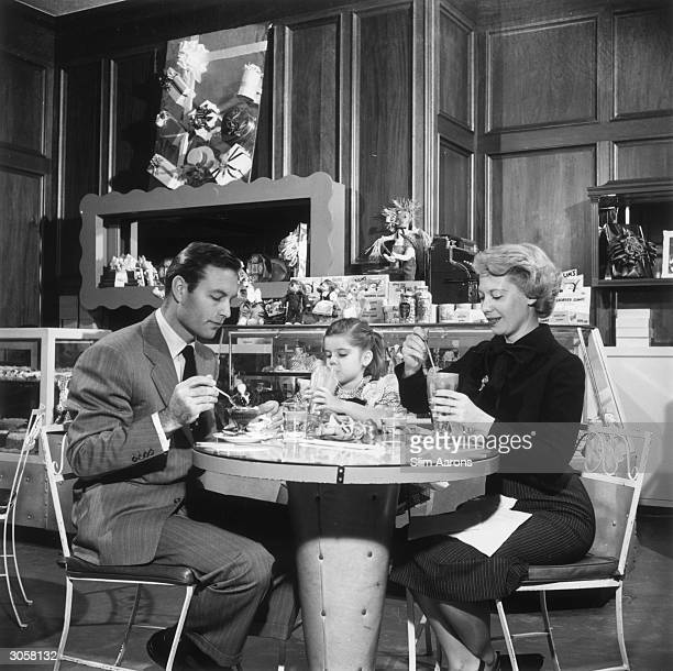 Film star George Montgomery his wife singer Dinah Shore and their daughter Melissa enjoying a sundae at Blums ice cream and candy store
