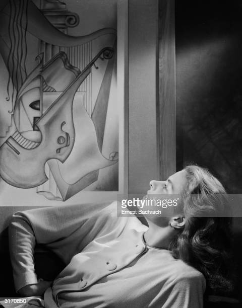Film star Ingrid Bergman studies a modernistic painting of musical instruments from a recling position.