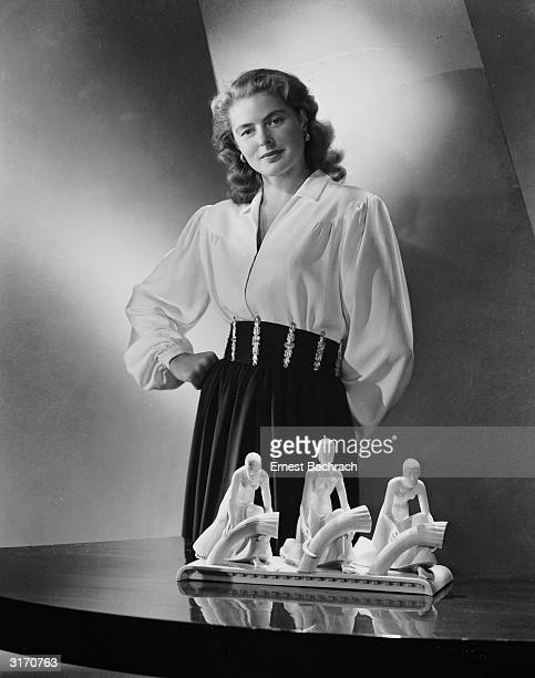 Film star Ingrid Bergman wearing a blouse with full sleeves gathered to tight cuffs a broad belt and softly draped skirt stands behind a table on...
