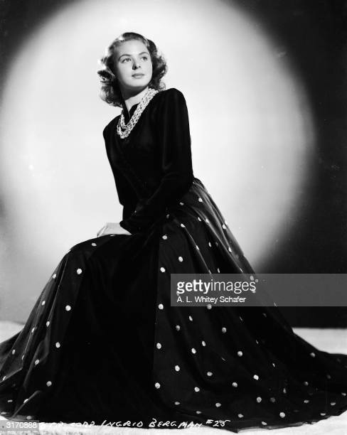 Film star Ingrid Bergman wearing a full length evening dress with plain tight fitting bodice long sleeves and full skirt with embroidered spots Round...