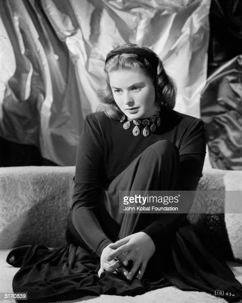 Film star Ingrid Bergman wearing a jewelled choker necklace with pendants over a plain, long sleeved, full length dress.
