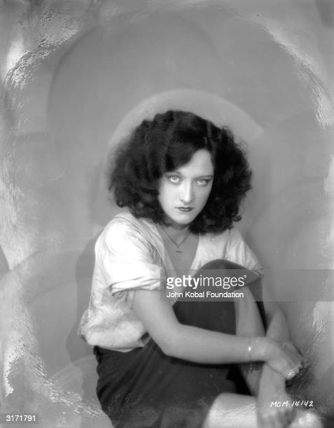 Film star Joan Crawford as she appears in the Lucien Hubbard film 'Rose Marie', with unstyled, frizzy, wavy, hair and wearing a small cross on a...