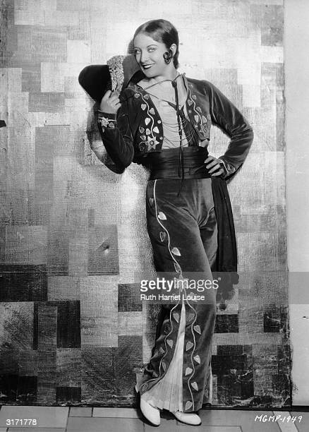 Film star Joan Crawford wears a Mexican style outfit with wide trousers cummerbund and short jacket Her hair is styled with a kisscurl over her ear