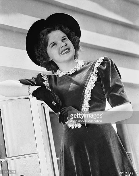 Film star Judy Garland wearing a hat with a heartshaped brim and a short sleeved velvet dress trimmed with lace