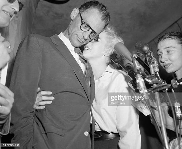 Film star Marilyn Monroe cuddles up to he fiance playwright Arthur Miller during a press interview in front to the Sutton Place apartment of the...